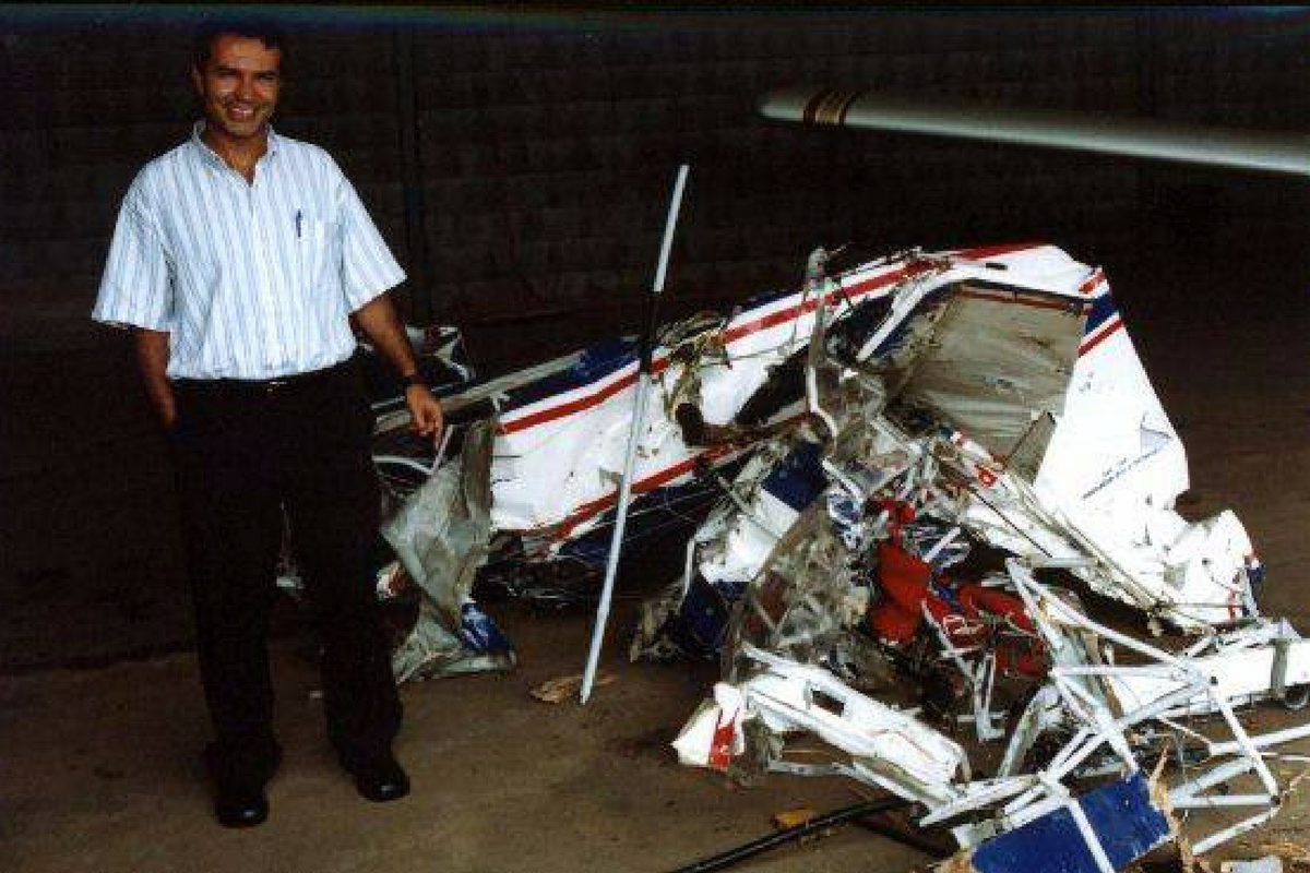 Paulo Henrique stands smiling next to a crashed airplane