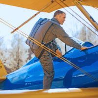 man climbs in vintage aircraft wearing Butler back parachute