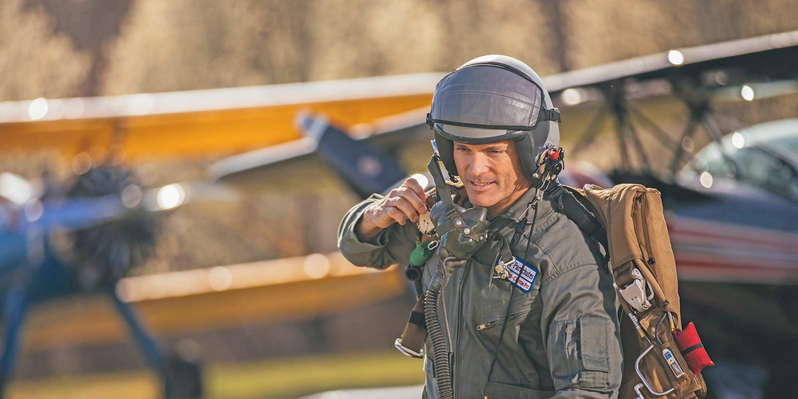 flight test pilot walks to plane wearing helmet and Butler emergency parachute