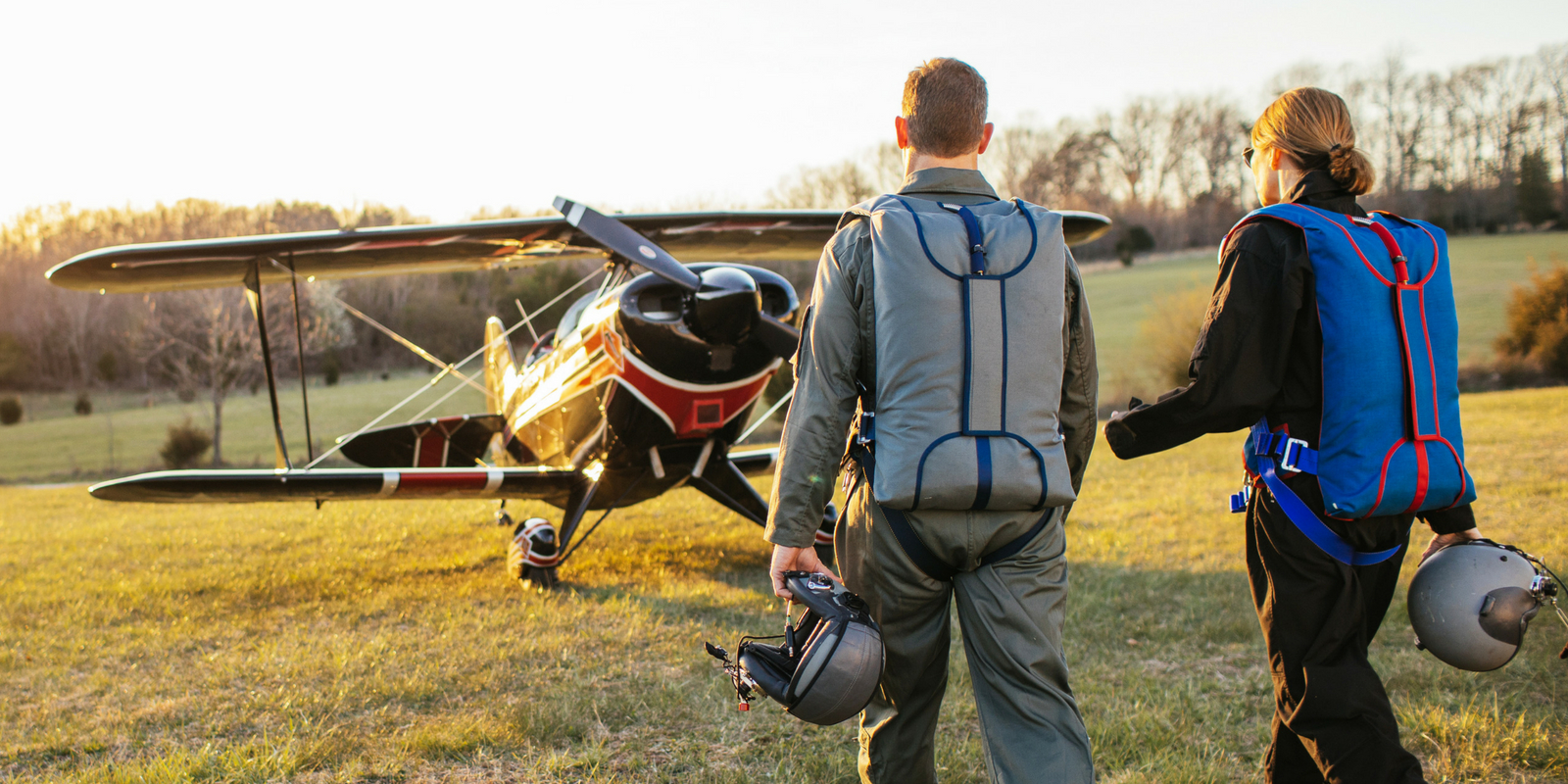 two pilots walk into the sunset wearing blue and gray Butler back parachutes