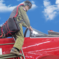 man climbs in small red aircraft wearing army green warbird seat parachute
