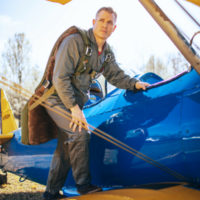 man climbs in vintage aircraft wearing army green warbird seat parachute